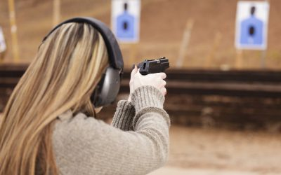 A woman at the shooting range aiming a gun at the target.